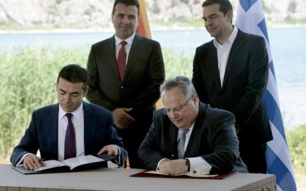 Министр иностранных дел Македонии Никола Димитров (слева) и его греческий коллега Никос Котзиас (справа) подписывают соглашение о переименовании бывшей югославской республики.