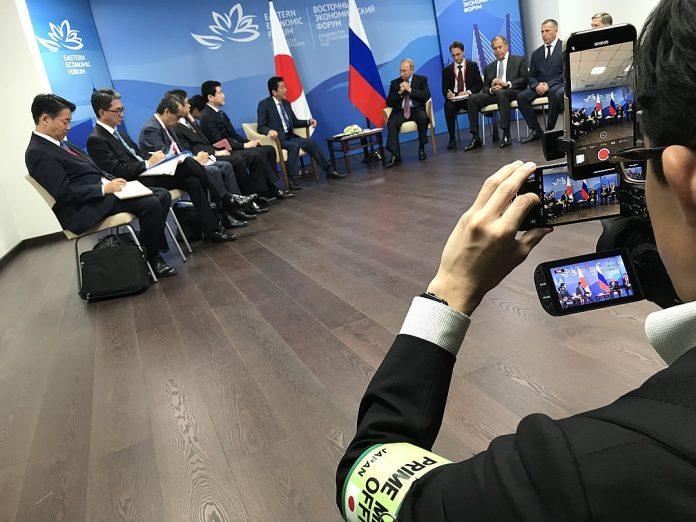 Японский журналист ведет видеотрансляцию сразу на нескольких мобильных платформах. Фото: Дмитрий СМИРНОВ