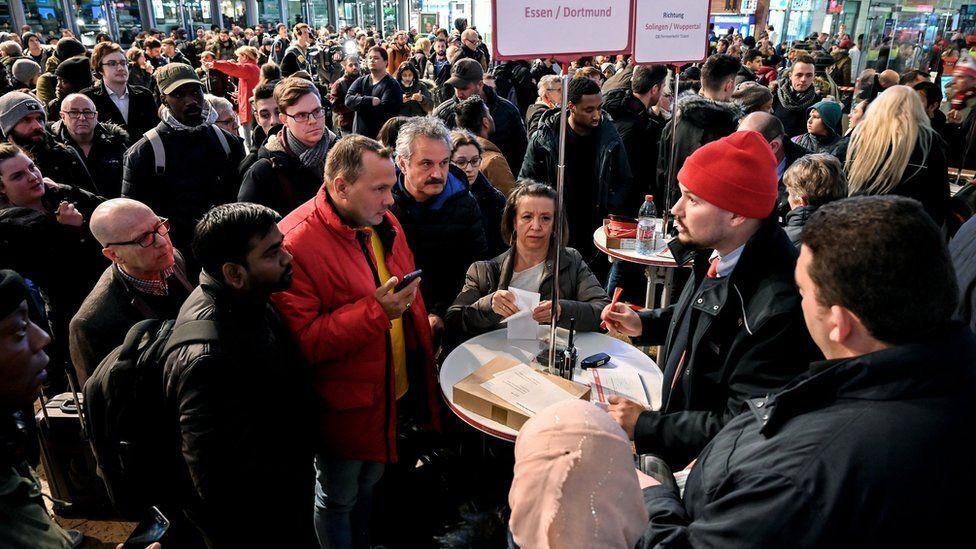 Пассажиры пытаются получить информацию о задержке поездов от сотрудников немецкой железной дороги на центральном вокзале Кельна